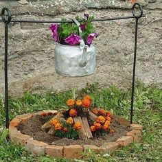 Flowers in coffee pot over fire pit
