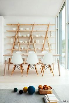 These ladder shelves are an unusual way to store tableware and cookware in the kitchen or dining area. The wood of the ladders blends well with the wood table.