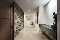 Feature stone continues from the exterior of the home through the large timber front door to create a stunning entrance.  Home designed and built by Urbane Projects, Perth.