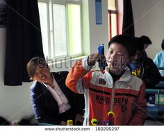 Baixiang County, China - April 2011: On April 27, 2011, baixiang County organized a test of physical and chemical experiments. Unidentified students are very careful to do each step of the trial. - stock photo