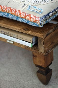 pallet bed/couch with smart use of space. white linen. Cool idea for a bench or coffee table to slide books in between pallet!