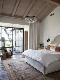 shades of neutrals. crystal chandelier. Linen headboard. velvet pillows. floor to ceiling curtains.