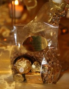 Party Favor Ideas (Can also be used to decorate tables) -- Gold foiled chocolates dropped into a clear cellophane bags & then sealed with a personalized gold seal.