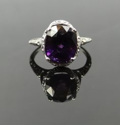 Delicate and dainty, this beautiful filigree ring from the Art Deco era is set with an amazingly deep, almost black raspberry colored violet Spinel.