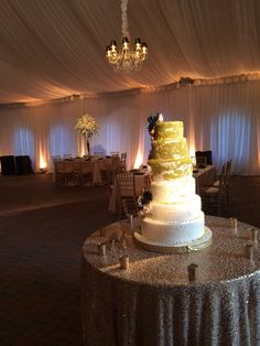 Spot lighting of beautiful cake, fabric up wash and crystal chandeliers in the Diana tent on the Biltmore Estate by Get Lit Special Event Lighting