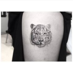 Fine line tiger tattoo on the right upper arm.