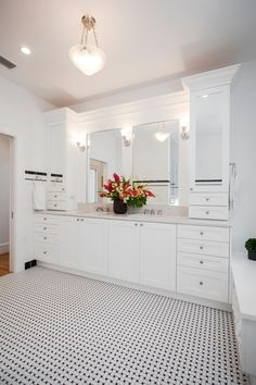 This bathroom remodel features a long white vanity with double sinks, extra cabinets and separate wall mirrors for simultaneous use. The space is essentially white — with two black wall stripes and a mosaic tile floor in black and white. The vanity's gray marble countertop coordinates with the color scheme.