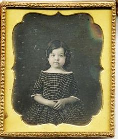 The boy wears his hair in ring curls of moderate length, but it is still parted on the side, showing that this is a boy child