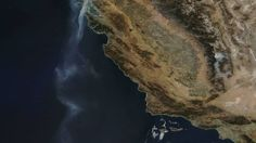 A photo captured Friday by NASA's Terra satellite shows a stream of smoke extending from the Wine County fire in Santa Rosa and Napa more than 500 miles south into the Pacific Ocean off San Diego. NASA