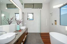 In this ensuite bath, there's a double vanity, bath and walk-in shower with built-in shelf, and the window on the right has been partially frosted for privacy.