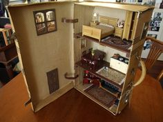 KALINDAS HOUSE A full dollhouse created inside a beautiful vintage suitcase. Three battery operated lights illuminate the home, which has a