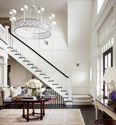 perfection- timber panelling, detailed timber stairs in contrast mahogany- double height entrance with  contemporary feature chandelier