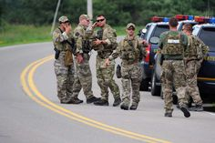 New York State Police officers gather along Route 20 after a possible sighting of the two murder convicts who escaped from a northern New York prison two weeks ago, on Sunday June 21, 2015, in Friendship, N.Y.  -    © Gary Wiepert/AP
