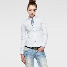 Slank gesneden, elegant overhemd met afneembare contrasterende das in de hals en een klassieke, rondlopende zoom. De gebogen naden volgen het lichaam.