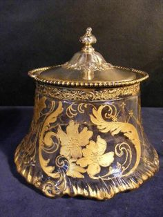"""A scarce antique Mount Washington Glass Co. Biscuit Jar with Pairpoint sliverplated and gilt mounts, rim having beaded design and handle. This is from their """"verona"""" line with heavy gilt Art Nouveau stylized  flowers and lattice design on colorless ground"""
