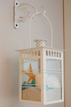 Hanging a lantern with sand, candle and beach finds.