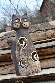 Kočka kudrnka Prořezávaná kočka z šamotové hlíny, pálená na vysokou teplotu. Barvena oxidy a glazurou. Vhodná do interiéru i do zahrady. Možnost vložit svíčku pro příjemnou atmosféru. Výška 44 cm. Tato kočička je zlevněná, má totiž lepenou spirálku vzadu, viz foto.