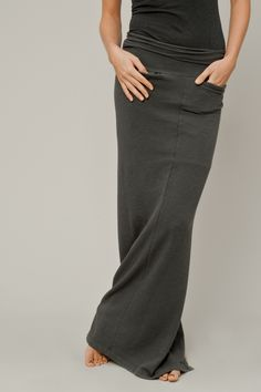 This casual maxi-tube skirt, in charcoal gray, is made of stretch knit and has two front slash pockets.