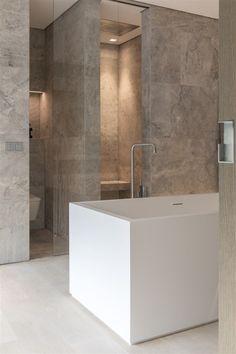 Lichte moderne badkamer met vrij ligbad en inloopdouche. Marmer en lichteiken