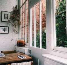 White walls, white painted brick, bright windows + wood furniture