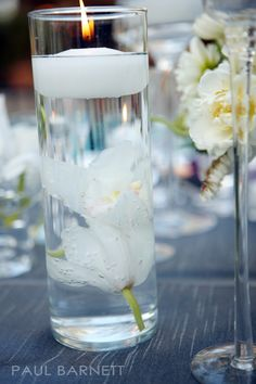 Classic detail of clear glass cylinder with sunken orchids beneath a floating candle
