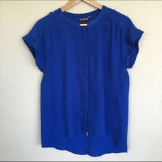 "Blue Button-Down Blouse Bold and chic royal blue blouse features hidden buttoned front, rolled short sleeves and a draped back. A polished look for work or going out tucked into a skirt or jeans. The back has a slit up the middle - a unique detail. Two buttons on the top of the shoulders. 100% polyester, machine wash cold. Perfect condition. Flat measurements: bust 18"", length 26"". Express Tops Button Down Shirts"