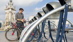 Un joven utiliza una de las estaciones de aparcamiento inteligente para bicicletas del sistema VadebikeBcn en Barcelona.
