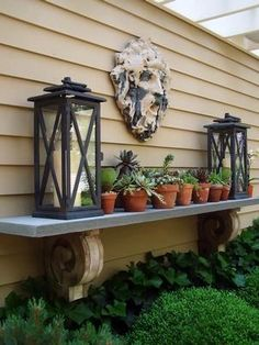 "An OUTDOOR MANTEL l!. What a great idea to fill up some back-of-the-house, boring wall space !  Use any option for  the Base ...bricks... ceramic pots ... sculptures.. etc, add a board for a shelf , add pots . lanterns with candles ( or battery operated candles )  . Hang a decorative piece , ( metal ,,, ceramic,.. wreath etc ) , over the middle of the "" Mantel  "" ."