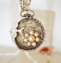 beautiful pendant/necklace with many details including pearls, sheet music, rhinestones and a white bird