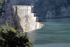 An anonymous band of artists paints a huge pair of scissors and a long dotted line on obsolete Matilija Dam near Ojai, CA