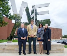 Penn State President Eric Barron, artist Jonathan Cramer, class gift chair Morgan Delaware and Molly Barron pose for a photograph at the 'We Are' Sculpture on the University Park campus. The four attended the Oct. 2 dedication of the gift of Penn State's class of 2013.