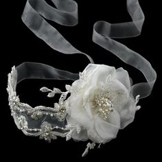 Adore your wedding day look with this elegant ribbon bridal headband. This accessory is composed of an ivory ribbon lace that carefully handcrafts a dainty flower, the side accenting feature. Additionally, unique beading, pearls and sparkling rhinestones illuminate this headpiece with breathtaking detail that is just simply unforgettable. This can also be worn around the waste to accentuate the wedding dress itself as a bridal belt. #timelesstreasure