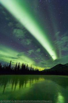 Green bands of northern lights, aurora borealis over a frozen lake, Brooks range, arctic, Alaska | Patrick J Endres