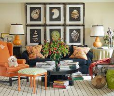 Tobi Fairley's Living Room   House & Home / orange chair, navy sofa with greek key trim, orange lamp, gallery wall of shells