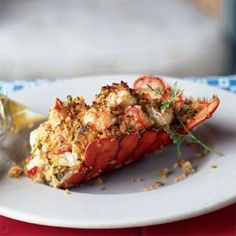 Stuffed Lobster 4 (1 1/4-pound) lobsters, cooked $  2 cups crushed reduced-fat round buttery crackers (such as Ritz)  1/4 cup chopped fresh parsley  3 tablespoons fresh Parmesan cheese  2 1/2 tablespoons butter, melted  2 tablespoons fresh lemon juice $  2 tablespoons Worcestershire sauce $  4 lemon wedges