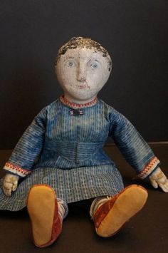 """This doll is 17"""" tall but still has the feeling of a small doll. She has a painted face over stockinette, I have only seen that once or twice in all the dolls I have had. She has a great raised nose that I think it is wood underneath. She has nice blue eyes and black painted curls around her face. She is all hand sewn. She has on a blue calico dress, blue and white striped socks and sweet red leather shoes. There is separation of the paint by her nose but it is the stretchy stockinette that…"""