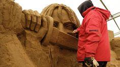"""Beim Sandskulpturen-Festival auf Rügen können die Besucher die Abbilder erfolgreicher Stars bestaunen, die lediglich aus den kleinen Mineralkörnern bestehen. Hier beispielsweise verpasst eine Künstlerin Uma Thurman den letzten Feinschliff. Cineasten erkennen anhand des Samurai-Schwerts sofort, dass es sich um eine Hommage an Quentin Tarantinos Kultfilm """"Kill Bill"""" handelt."""
