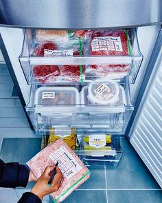 Skuffer i en fryser, som er trukket ud og fyldt med madvarer, der er perfekt organiseret i poser og bokse med etiketter.