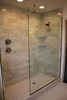 the doorless glass shower...doorless glass shower, marble subway tile, rain head and shower head. Added recessed lighting and a new hexagon white tile floor with light gray grout.