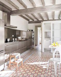 Cuisine moderne en inox dans une pièce au plafond à poutre apparentes peintes en gris