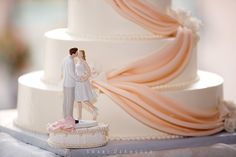 In this unique ceramic wedding cake topper, a bride in a short white dress reaches up to kiss her groom, who is donning a grey suit. The piece topped a gorgeous and elegant white tiered wedding cake with pale pink - almost peach - icing draped like luxurious fabric across the sides and finished with sculpted white icing roses. #Looksy #ORLYsmartGELS