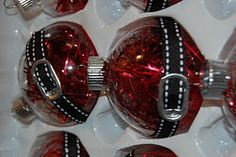 A Cute ornament using metallic red shreds, a pop top and ribbon.