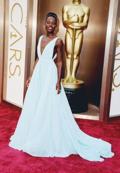 Best Supporting Actress winner Lupita Nyong'o in a custom light blue silk pleated Prada gown; Fred Leighton headband, earrings, bracelet, and rings; Prada clutch and satin platform sandals at the 86th Annual Academy Awards. #LupitaNyongo #Oscars #RedCarpet