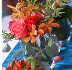 Short, square, glass vases were placed on a turquoise table runner and filled with coral roses, orange Mokara orchids, and light green leaves