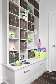 Basement playroom features floor to ceiling light grey built-ins boasting stacked open cubbies