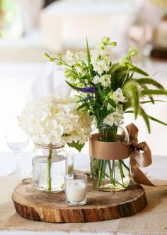 Floral centerpiece in canning jars on wooden slices #wedding