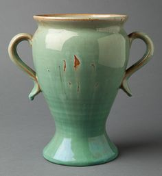 "Vase,     Genuine Bybee (1922-1926),       Slip glazed stoneware,     8- 3/8"" tall		.         Hand thrown, light green slipped high glaze vase with two scrolling handles and ink stamped logo mark underneath. Potted in Waco, Kentucky. The vase is in fine condition with a color contamination imperfection (when fired) on one side of the vase, which is visible in one of the images."