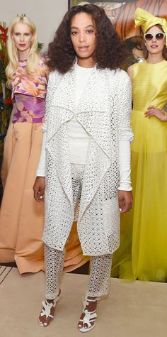 Solange Knowles hit the Christian Siriano Resort 2016 presentation in head-to-toe white, which consisted of a lacquered laser-cut and pants with a brocade tee, all by Christian Siriano, and white strappy sandals.