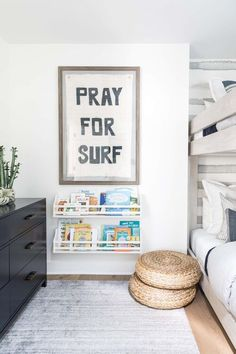 A 'Pray For Surf' art print hangs in a brown wooden frame over stacked white bookshelves fixed over seagrass poufs positioned in a gray boys' bedroom on a gray rug beside white weathered bunk beds. Surf Bedroom, Kids Bedroom, Surf Nursery, Boys Surf Room, Surfer Room, Big Boy Bedrooms, Boy Rooms, Grey Boys Rooms, Kids Rooms