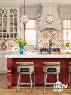 A dark red painted kitchen island pairs well with encaustic Spanish wall tile, hanging rattan globe pendants and navy and rattan kitchen stools. Take a full house tour on HGTV.com.